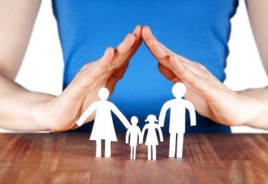 both hands of woman on top of paper cut out of family