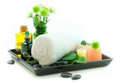 Rolled towel on plate with spa oils