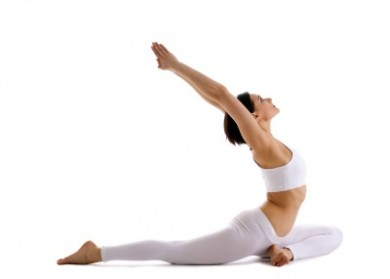 Young woman training in yoga asana - pigeon pose