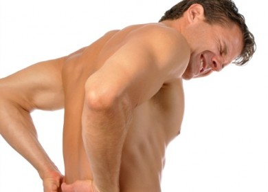Topless athletic male suffering from excrutiating lower back pain